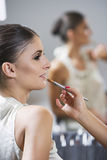 Profile of woman sitting in makeup lip gloss application Stock Photography