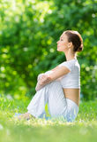 Profile of woman sitting on mat in park Royalty Free Stock Image