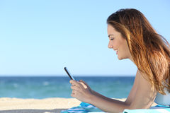 Profile of a woman texting in a smart phone on the beach Stock Image