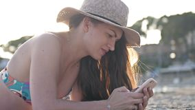 Profile of a woman texting in a smart phone on the beach with the sea in the background stock footage