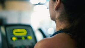 Profile of woman working out on elliptical machine at gym stock footage