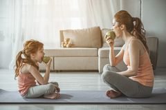 Woman and girl are looking at each other and eating stock photography