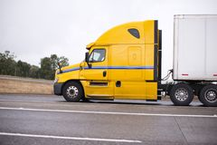 Profile of yellow big rig semi truck with semi trailer running o. Profile of yellow modern American big rig semi truck tractor for long haul freights Royalty Free Stock Photo