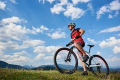Profile of young athletic tourist biker in professional sportswear starting to cycle a bike royalty free stock images