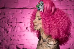 Profile of young attractive caucasian girl model with afro style curly bright pink hair, tattooed face and flowers woven into her royalty free stock photo
