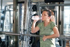 Profile young brunette woman going to drink some water from plastic bottle after workout stock photo