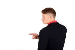 Profile of a young business man wearing a suit and a red shirt looking to the side and pointing. Royalty Free Stock Photo