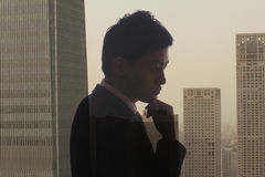 Profile of young businessman contemplating, double exposure of cityscape, Beijing Royalty Free Stock Photo