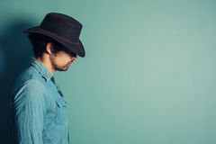Profile of young cowboy. Profile shot of a young cowboy standing against a blue wall Stock Photo