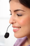 Profile young female receptionist wearing headset Stock Image
