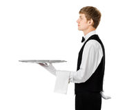 Profile of young handsome waiter holding empty tray with copy sp Stock Photography
