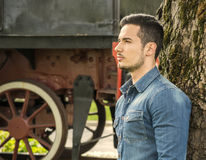 Profile of young man in denim shirt near old train, against tree Stock Photos