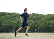 Profile of a young man jogging outdoors Stock Photo