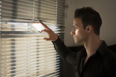 Profile of young man peeking through venetian blinds Royalty Free Stock Photo