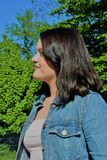 Profile of a young satisfied woman in the park.  Royalty Free Stock Image