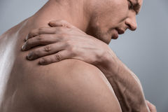 Profile of young shirtless man with shoulder pain. Stock Images