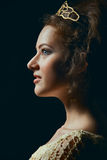 Profile of young woman on black background. Profile of majestic young woman wearing tiara on black background Royalty Free Stock Photography