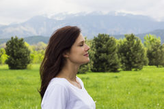 Profile of young woman with eyes closed breathing fresh air in the mountains Stock Images