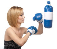 Profile of a young woman kicking a punching bag Royalty Free Stock Photography