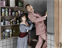 Profile of a young woman pushing out a young man from a domestic kitchen Stock Image