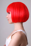 Profile of young woman in red wig Royalty Free Stock Image