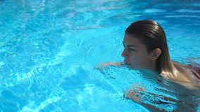 Profile of young woman refreshing and swimming in pool of hotel with blue clear water. Beautiful girl floating at basin stock footage