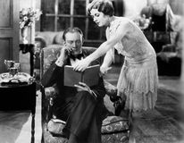 Profile of a young woman showing a book to a man sitting in an armchair Royalty Free Stock Images