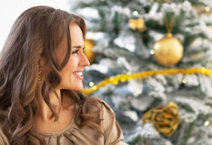 Profile young woman sitting near christmas tree Royalty Free Stock Photo