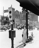 Profile of a young woman standing near a stop light. (All persons depicted are no longer living and no estate exists. Supplier grants that there will be no Royalty Free Stock Image