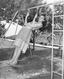 Profile of a young woman swinging on a swing in a garden Stock Photos