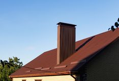Profiled sheeting chimney on the metal tile roof with rain gutters and snow guards. Brown profiled sheeting chimney on the metal tile roof with rain gutters and royalty free stock image