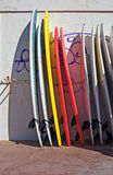 Profiled surf board. Close up of colorful surfboards upright profiled with a white wall with a graffiti in the background Stock Photography