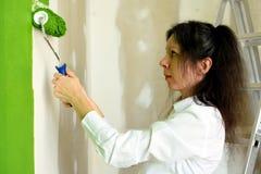 Profilen av en le nätt ung kvinna håller rullen med två händer och försöker försiktigt att måla den gröna innerväggen i royaltyfri bild