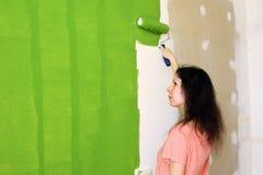 Profilen av en nätt ung kvinna i rosa t-skjorta målar försiktigt den gröna innerväggen med rullen i ett ny hem och utvärder royaltyfri fotografi