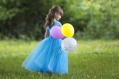 Profilera den hellånga ståenden av den nätta lilla blonda långhåriga flickan i lång blåttklänning med färgrika ballonger som står arkivbild