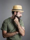 Profilera sikten av den bärande sugrörhatten för den ledsna skäggiga mannen som bort ser Arkivbild