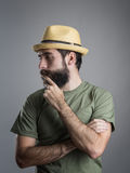 Profilera sikten av den bärande sugrörhatten för den unga eftertänksamma skäggiga mannen som trycker på hans skägg Arkivfoton