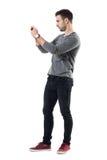 Profilera sikten av den hållande mobiltelefonen för den allvarliga unga tillfälliga mannen som tar fotoet royaltyfri foto