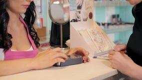 Profilera sikten av en nätt ung kvinna som betalar med en kreditkort på ett lager stock video