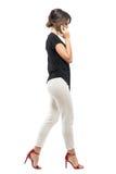 Profilera sikten av upptagen affärskvinnaanställd som går och talar på telefonen som ner ser royaltyfria bilder