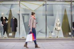 Profilera skottet av den unga kvinnan med shoppingpåsar som ser fönsterskärm Arkivfoto