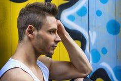 Profilera skottet av den unga mannen bredvid ljusa kulöra grafitti Arkivbilder