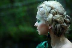 Profilera ståenden av den unga nymfkvinnan nära vattenfallet i skogen Arkivfoto