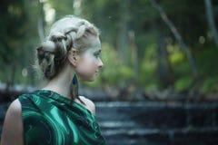 Profilera ståenden av den unga nymfkvinnan nära vattenfallet i skogen Royaltyfria Foton