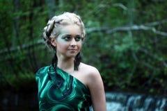 Profilera ståenden av den unga nymfkvinnan nära vattenfallet i skogen Arkivfoton