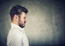 Profilera ståenden av en skäggig man med grimasen av avsmak arkivfoto