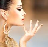 Profilera ståenden av modekvinnan med härliga guld- mani Arkivfoton