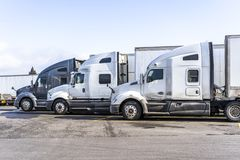 Profiles of big rigs semi trucks with semi trailers stand on wide parking lot of truck stop. Big rigs commercial cargo haulers Semi Trucks with different semi royalty free stock photo