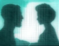 Profiles of man and woman behind blue glass Royalty Free Stock Photo