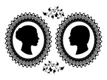 Profiles of man and woman in ornate frame. Stock Images